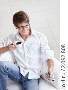 Купить «Молодой человек с пультом и чашкой кофе», фото № 2092808, снято 13 сентября 2010 г. (c) Raev Denis / Фотобанк Лори