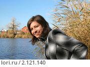 Молодая красивая девушка улыбается на фоне голубого озера, на природе солнечным осеним днем, фото № 2121140, снято 31 октября 2010 г. (c) Сергей Кузнецов / Фотобанк Лори
