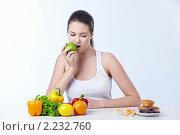 Купить «Нелегкий выбор. Девушка кушает яблоко и смотрит на сладости», фото № 2232760, снято 1 декабря 2010 г. (c) Raev Denis / Фотобанк Лори
