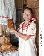 Купить «Пожилая женщина с хлебом у традиционной русской печи», фото № 2269540, снято 6 июля 2010 г. (c) Дарья Филимонова / Фотобанк Лори
