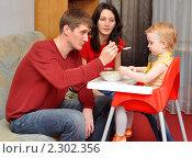 Купить «Родители кормят двухлетнюю дочку манной кашей», фото № 2302356, снято 26 января 2011 г. (c) Анна Мартынова / Фотобанк Лори