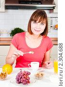Купить «Молодая женщина добавляет сахар в кофе», фото № 2304688, снято 27 ноября 2009 г. (c) Валерия Потапова / Фотобанк Лори