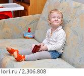 Купить «Довольная девочка (2 года) на диване с загранпаспортом», фото № 2306808, снято 26 января 2011 г. (c) Анна Мартынова / Фотобанк Лори