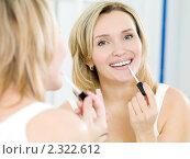 Красивая девушка наносит блеск на губы. Стоковое фото, фотограф Валуа Виталий / Фотобанк Лори