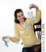 Беременная женщина радостно смотрит на детские вещи. Стоковое фото, фотограф Инна Додица / Фотобанк Лори