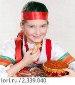 Купить «Девочка в русской национальной одежде с миской красной икры и блином в руке», фото № 2339040, снято 11 февраля 2011 г. (c) RedTC / Фотобанк Лори