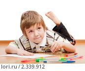 Купить «Маленький мальчик рисует или пишет разноцветными ручками, лежа на полу», фото № 2339912, снято 4 февраля 2011 г. (c) Илья Андриянов / Фотобанк Лори