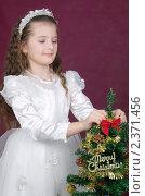Купить «Девочка в нарядном белом платье украшает новогоднюю елку», фото № 2371456, снято 23 сентября 2018 г. (c) RedTC / Фотобанк Лори
