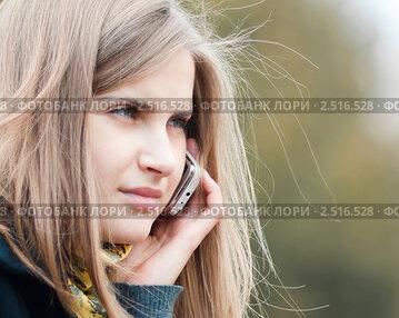 Девушка на улице разговаривает по мобильному телефону. Крупный план