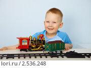 Мальчик играет с игрушечной железной дорогой. Стоковое фото, фотограф pzAxe / Фотобанк Лори