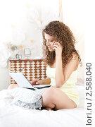 Девушка с телефоном и ноутбуком на кровати. Стоковое фото, фотограф Анисимов Леонид / Фотобанк Лори