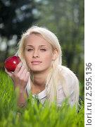 Купить «Портрет девушки, лежащей на траве с яблоком в руке», фото № 2595136, снято 7 мая 2011 г. (c) Андрей Батурин / Фотобанк Лори