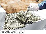 Купить «Каменщик укладывает раствор на бетонный блок», фото № 2611212, снято 16 октября 2018 г. (c) Дмитрий Калиновский / Фотобанк Лори