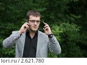 Бизнесмен говорит по двум мобильным телефонам. Стоковое фото, фотограф Ольга Герасимова / Фотобанк Лори