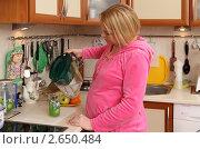 Купить «Беременная молодая женщина наливает фильтрованную воду на кухне», эксклюзивное фото № 2650484, снято 6 февраля 2011 г. (c) Дмитрий Неумоин / Фотобанк Лори
