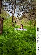 Девушка в свадебном платье сидит в траве с книгой. Стоковое фото, фотограф Сергей Павлов / Фотобанк Лори