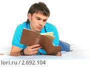 Купить «Студент читает записи в ежедневнике», фото № 2692104, снято 4 апреля 2020 г. (c) Александр Макаров / Фотобанк Лори