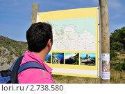 Турист смотрит на дорожную карту, путешествуя с рюкзаком (2011 год). Редакционное фото, фотограф valentina vasilieva / Фотобанк Лори