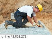 Купить «Рабочий кладет тротуарную плитку», фото № 2852272, снято 22 апреля 2018 г. (c) Дмитрий Калиновский / Фотобанк Лори