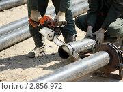 Рабочие отрезают трубу ПВХ бензопилой. Стоковое фото, фотограф Клыкова Инна / Фотобанк Лори