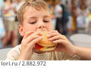 Купить «Мальчик ест большой гамбургер», фото № 2882972, снято 4 июля 2010 г. (c) Losevsky Pavel / Фотобанк Лори