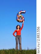 Купить «Девушка держит в руке надувную цифру 6», фото № 2883556, снято 7 мая 2010 г. (c) Losevsky Pavel / Фотобанк Лори