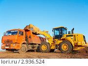 Экскаватор загружает землю в кузов самосвала. Стоковое фото, фотограф Дмитрий Калиновский / Фотобанк Лори