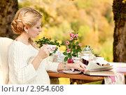 Беременная женщина сидит в летнем саду за столиком, пьет чай и читает книгу. Стоковое фото, фотограф Екатерина Штерн / Фотобанк Лори