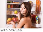 Девушка берет яблоко в холодильнике. Стоковое фото, фотограф Майя Крученкова / Фотобанк Лори