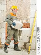 Купить «Строитель устанавливает поризованный блок на стену», фото № 2977080, снято 12 декабря 2019 г. (c) Дмитрий Калиновский / Фотобанк Лори