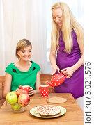 Купить «Чаепитие на кухне. Девушка наливает своей подруге чай», фото № 3021576, снято 23 июля 2018 г. (c) Петр Малышев / Фотобанк Лори
