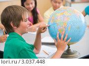 Купить «Ученик смотрит на глобус, показывает на нем страны, урок географии», фото № 3037448, снято 1 марта 2000 г. (c) Monkey Business Images / Фотобанк Лори