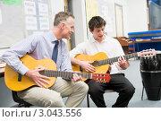 Купить «Ученик и учитель играют на гитаре в музыкальном классе», фото № 3043556, снято 13 февраля 2007 г. (c) Monkey Business Images / Фотобанк Лори