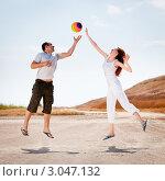 Мужчина и женщина играют в мяч на открытом воздухе. Стоковое фото, фотограф IEVGEN IVANOV / Фотобанк Лори