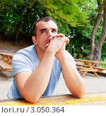Задумчивый мужчина сидит за столом на открытом воздухе. Стоковое фото, фотограф IEVGEN IVANOV / Фотобанк Лори