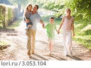 Семья на прогулке. Папа несет дочку на плече, сын держит родителей за руки. Стоковое фото, фотограф Monkey Business Images / Фотобанк Лори