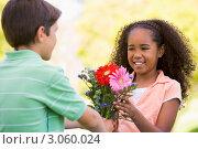 Мальчик дарит девочке букет цветов. Стоковое фото, фотограф Monkey Business Images / Фотобанк Лори