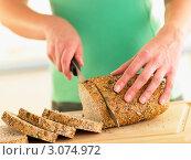 Купить «Женщина режет зерновой хлеб», фото № 3074972, снято 14 ноября 2007 г. (c) Monkey Business Images / Фотобанк Лори
