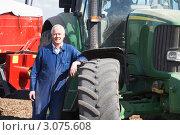 Купить «Тракторист облокотился на колесо трактора», фото № 3075608, снято 19 мая 2000 г. (c) Monkey Business Images / Фотобанк Лори