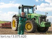 Купить «Тракторист в зеленом комбинезоне на фоне трактора», фото № 3075620, снято 19 мая 2000 г. (c) Monkey Business Images / Фотобанк Лори