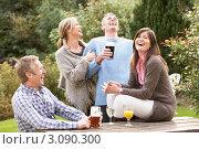 Купить «Четверо друзей смеются и выпивают в саду», фото № 3090300, снято 1 октября 2009 г. (c) Monkey Business Images / Фотобанк Лори