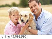Купить «Мальчик, отец и собака на фоне осеннего поля», фото № 3098996, снято 20 июля 2010 г. (c) Monkey Business Images / Фотобанк Лори