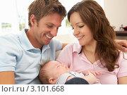 Купить «Счастливые молодые родители смотрят на новорожденного спящего  младенца», фото № 3101668, снято 19 июля 2010 г. (c) Monkey Business Images / Фотобанк Лори