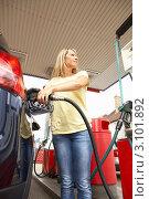 Купить «Женщина заправляет машину на заправочной станции», фото № 3101892, снято 30 июня 2010 г. (c) Monkey Business Images / Фотобанк Лори