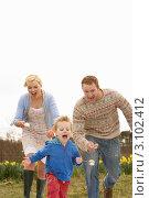 Купить «Счастливая пара с маленьким сыном гуляют в поле с нарциссами и ищут пасхальные яйца», фото № 3102412, снято 21 апреля 2010 г. (c) Monkey Business Images / Фотобанк Лори