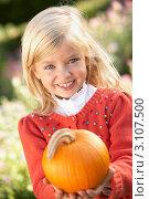 Маленькая девочка держит в руках спелую, желтую тыкву. Стоковое фото, фотограф Monkey Business Images / Фотобанк Лори