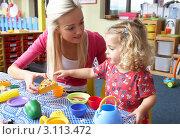 Купить «Воспитательница и маленькая девочка играют вместе в детском саду», фото № 3113472, снято 16 октября 2010 г. (c) Monkey Business Images / Фотобанк Лори