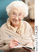 Купить «Улыбающаяся пожилая женщина разгадывает кроссворд, сидя в кресле», фото № 3114200, снято 7 января 2011 г. (c) Monkey Business Images / Фотобанк Лори