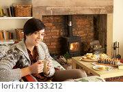 Купить «Молодая темноволосая девушка пьет чай на диване возле камина», фото № 3133212, снято 5 октября 2010 г. (c) Monkey Business Images / Фотобанк Лори