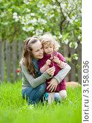 Молодая женщина с дочерью изучают через лупу одуванчик весной. Стоковое фото, фотограф yarruta / Фотобанк Лори